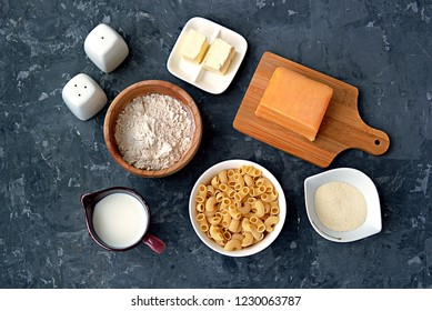 Ingredients for the preparation of mac and cheese: dry pasta, orange cheddar cheese, wheat flour, bread crumbs, milk, butter, salt, pepper