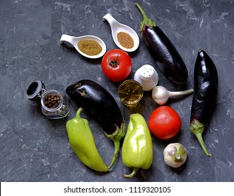 Ingredients for preparation of salad  from eggplants, tomatoes and sweet peppers on a dark gray concrete background. Eggplants, tomatoes, sweet peppers, garlic, spices, salt, olive oil.