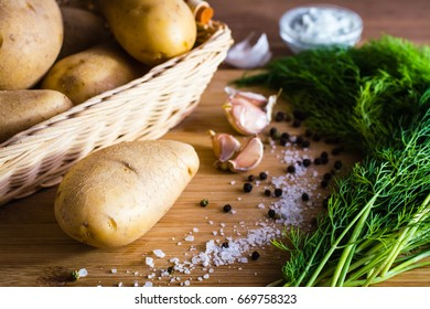 Ingredients to prepare potato dishes: tubers, garlic, dill, pepper and salt