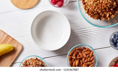 Ingredients for preparing healthy breakfast - berries, cereal flakes, muesli, banana, honey, almonds, walnuts on white. Top view.