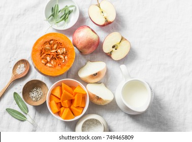 Ingredients for pumpkin apple soup on white background, top view. Pumpkin, apples, cream, onion, sage - ingredients for a healthy lunch