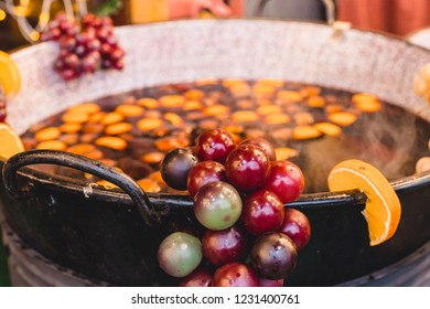 Ingredients for punch and mulled wine in a cauldron on a Christmas market. Ingredients citrus and spices are in the drink, grapes and aplesine hang on the cauldron. Process of cooking winter hot drink