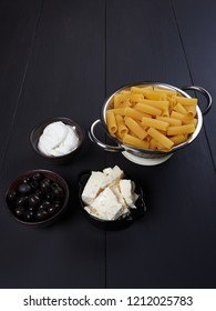 Ingredients for rigatoni with cream, gorgonzola, and olives, a vegetarian plate known in Itlay as pasta alla cenere, literally meaning pasta with ash