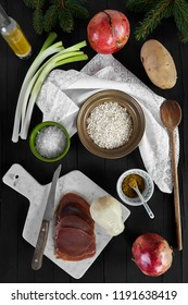Ingredients for the risotto recipe with scamorza cheese and smoked tuna fish. Photographed from above, on a black wooden background.