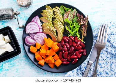 ingredients for salad, baked pumpkin, avocado and red beans on black plate