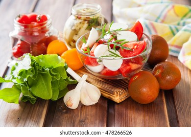 ingredients for salad - cheese, tomatoes, greens and garlic on a table, selective focus