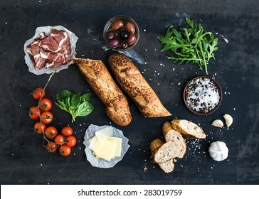 Ingredients for sandwich with smoked meat, baguette, basil, arugula, olives, cherry-tomatoes, parmesan cheese, garlic and spices over black grunge background. Top view
