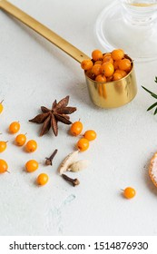 Ingredients for sea buckthorn tea on white concrete background. Concept of healthy recipe for warm beverages