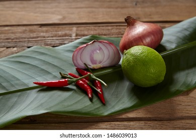 Ingredients set for Thai spicy soup (Tom-yum) include lemon, red chili ,red onion lemongrass and green lime on wood table.