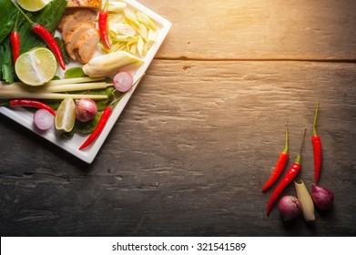 Ingredients set for Thai spicy soup (Tom-yum) include lemon, galangal, red chili, red onion, lemongrass, and kaffir lime leaf on wood table in low key morning scene with blank area for text or message