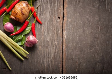 Ingredients set for Thai spicy soup (Tom-yum) include lemon, galangal, red chili, red onion, lemongrass, and kaffir lime leaf on wood table in morning scene with blank area for text or message