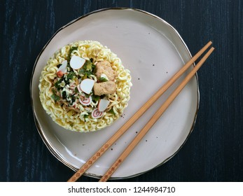 Ingredients for shin noodles in a blue bowl, with white and blue chopsticks, on dark blue background, flatlay