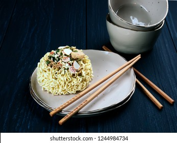 Ingredients for shin noodles in a blue bowl, with white and blue chopsticks, on dark blue background