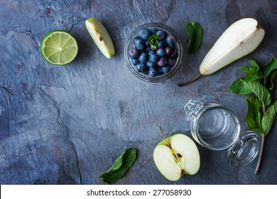 Ingredients for smoothie from apple, pear and blueberry on the stone table