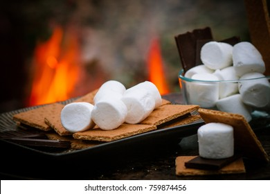 ingredients for smores in front of a fire