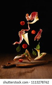Ingredients for snack with bread, jamon and vegetables flying above wooden table surface