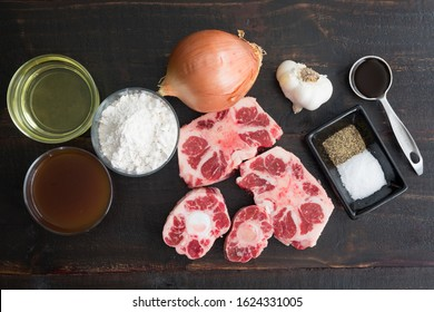 Ingredients for Southern Smothered Oxtails: Raw beef oxtail, onion, garlic, and other ingredients used to make braised oxtails and gravy
