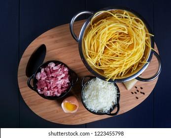 Ingredients for spaghetti carbonara: fresh spaghetti, grated pecorino romano, bacon (or guanciale), egg yolk, black peppercorns, top view