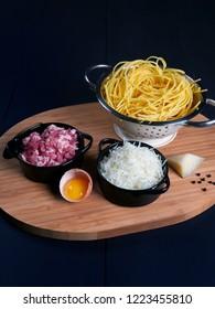 Ingredients for spaghetti carbonara: fresh spaghetti, grated pecorino romano, bacon (or guanciale), egg yolk, black peppercorns