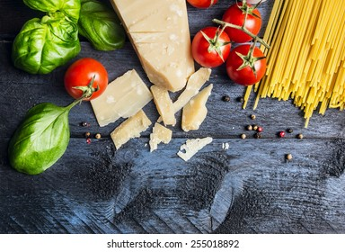 Ingredients for spaghetti with tomato sauce: basil, tomatoes,parmesan on blue wooden background , top view,place for text