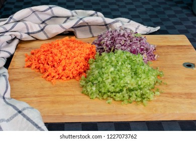ingredients of the spezzatino, a traditional italian cepice. Onion, celery and carrots on a wood cutting board - Shutterstock ID 1227073762