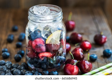 Ingredients for Summer Slushy from Blueberries, Cherries, Lemon and Ice in the Jar, on dark rustic background