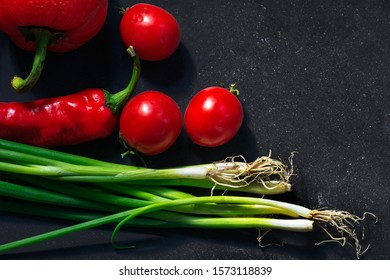 Ingredients for tasty eat making: tomatoes, onion. pepper on dark background, top view, border. Healthy, diet or vegetarian food concept