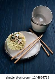 Ingredients for tempura udong noodles, with wooden chopsticks, on dark blue background