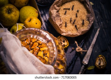 Ingredients for tinctures: Fruits, twigs quince, sugar, cloves, vanilla on a wooden table