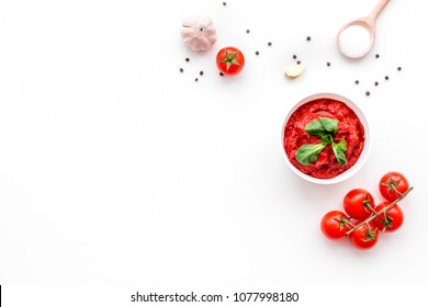 Ingredients for tomato sauce. Cherry tomatoes, garlic, green basil, black pepper, salt in spoon on white background top view copy space