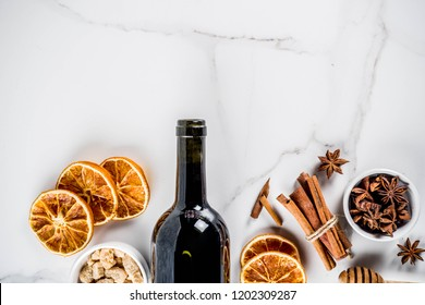 Ingredients for traditional autumn drink, mulled wine cocktail - red wine, stale oranges, cane sugar, honey, cinnamon, spices, anise, on white marble background, top view space for text