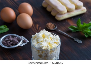 Ingredients of traditional italian dessert tiramisu - ladyfingers cake, eggs, mascarpone creme, cocoa, chocolate and peppermint on wooden background