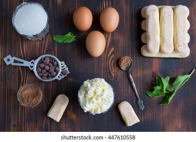 Ingredients of traditional italian dessert tiramisu - ladyfingers cake, eggs, sugar, mascarpone creme, cocoa, chocolate and peppermint on wooden background, top view.