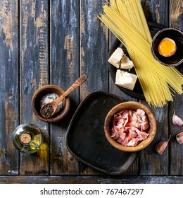 Ingredients for traditional italian pasta alla carbonara. Uncooked spaghetti, pancetta bacon, parmesan cheese, egg yolk  in olive wood bowls over old plank background. Top view, space. Square image