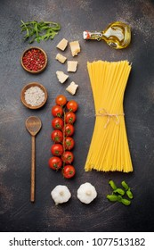 Ingredients for traditional Italian pasta dish.  Raw spaghetti, parmesan cheese, olive oil, garlic, basil leaves, pepper, cherry tomatoes on old dark stone background.  Selective focus. Top view.