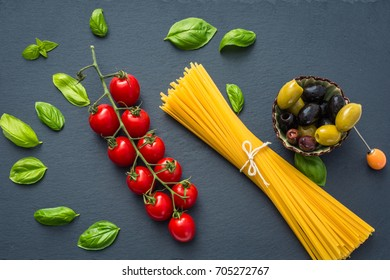 Ingredients of traditional Italian pasta on a dark background, top view.