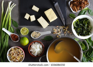 ingredients for traditional japanese miso soup. dashi, miso paste, wakame seaweeds, steamed rice, mushrooms, greens and spices at concrete kitchen table, view from above