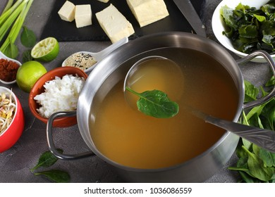ingredients for traditional japanese miso soup. tofu, dashi in a stainless casserole, miso paste, seaweeds, rice, mushrooms, sprouts, greens and spices on concrete table, view from above, close-up