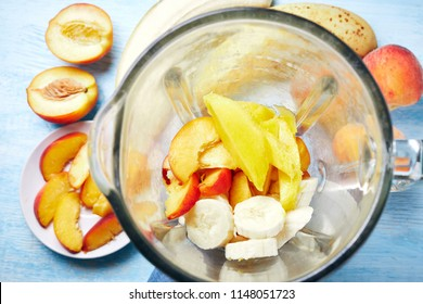 Ingredients for a tropical fruit smoothie with mango, peach and banana. High angle view image of blender jar with sliced peach, banana and mango. Various fruits in a blender for making a perfect