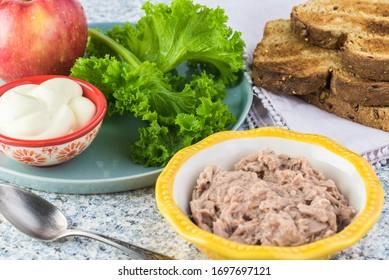 Ingredients for tuna salad: caned tuna, cut onion, apple, mayonnaise.