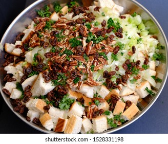 Ingredients for turkey bread stuffing in bowl ready to mix. Bread, onions, celery, raisins, parsley, pecans. Shotbfrom above