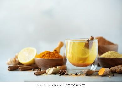 Ingredients for turmeric hot tea on grey background. Healthy ayurvedic drink with lemon, ginger, cinnamon, turmeric. Immune boosting remedy.