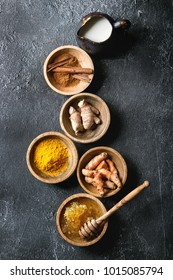Ingredients for turmeric latte. Ground turmeric, curcuma root, cinnamon, ginger, honeycombs in wooden bowls, jug of milk over black texture background. Top view, copy space