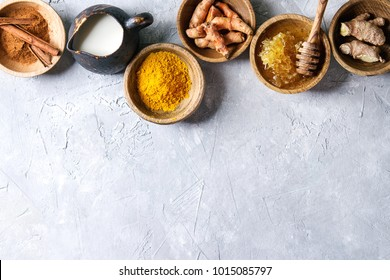 Ingredients for turmeric latte. Ground turmeric, curcuma root, cinnamon, ginger, honeycombs in wooden bowls, jug of milk over grey texture background. Top view, copy space