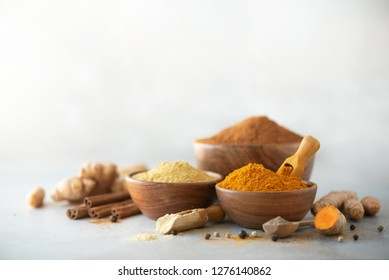 Ingredients for turmeric latte. Ground turmeric, curcuma root, cinnamon, ginger, black pepper on grey background. Spices for ayurvedic treatment. Alternative medicine concept.