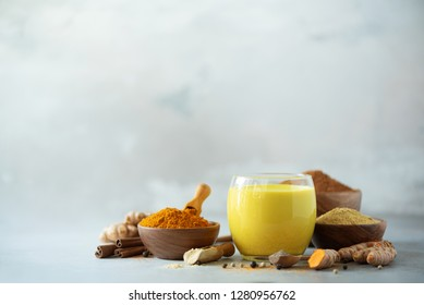 Ingredients for turmeric latte. Turmeric powder, curcuma root, cinnamon, ginger over grey background. Copy space, square crop. Spices for ayurvedic treatment. Alternative medicine concept.