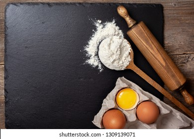 Ingredients and utensils for baking. Spoon with flour, eggs, rolling pin on a black slate background. Top view, selective focus, copy space