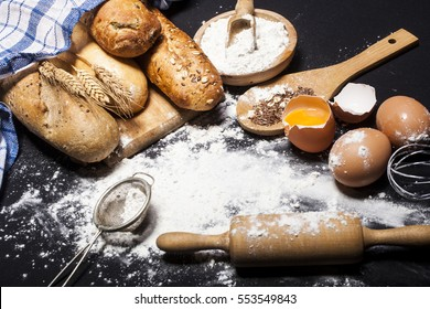 Ingredients and utensils for the preparation of bakery products - flour, eggs, rolling pin, whisk, strainer, bread - on black table with free copy space