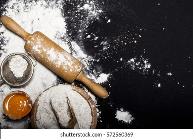 Ingredients and utensils for the preparation of bakery products - flour, dough, eggs, rolling pin, whisk, strainer, bread - on black table with free copy space