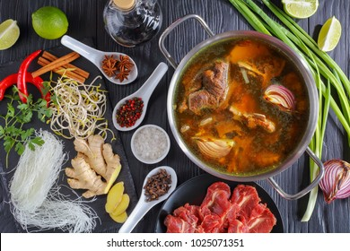 ingredients of Vietnamese soup Pho Bo, with raw beef, bone broth in a stainless pan, soy sprouts, spices, baked onion, rice noodle, fresh coriander and mint on black wooden table, view from above